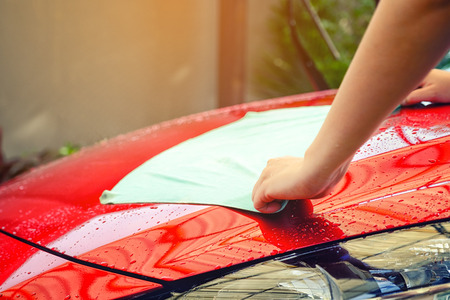 hand women hold water over the red car for washing with microfiber cloth Stock Photo