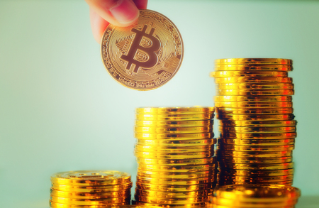 Hand hold a single bitcoin over Stack of glod bitcoins, Cryptocurrency concept. Virtual currency digital payment system