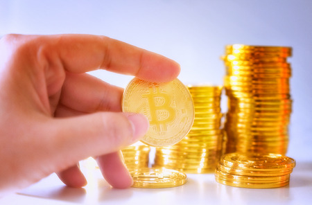 Soft Focus Hand hold a single bitcoin over Stack of glod bitcoins, Cryptocurrency concept. Virtual currency digital payment system