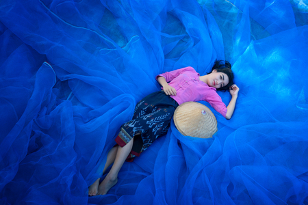 Beautiful Thai woman is harvesting indigo on blue net floor