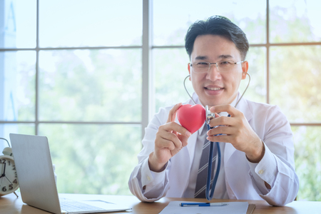 Heart in the hands of the doctor with stethoscope who mediates health. Love concept. Health concept. selective focus.