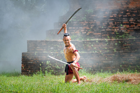 Thai legend warrior action. Ancient soldier holding swords ready to fighting. He is a hero of Thai in the past.