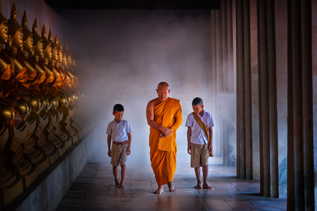 Monk and tow boy student at Golden buddha statue, Makhabucha day, Visakabucha, Ansahabucha, way in old temple with a lot of buddha image in Temple Ayutthaya Thailand