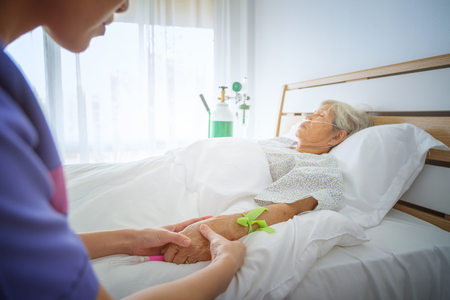 Nurse check pulse from hand of patients on the bed in the hospital room blur background, Intensive therapy concept