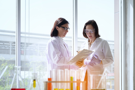 Young female scientist standing with techer in lab worker making medical research in modern laboratory. Scientist holding documents folder with analysis results.