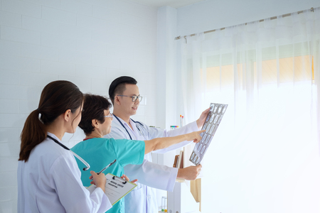 Male and female doctors consulting in bright office, discussing x-ray image to his colleagues at private clinic.