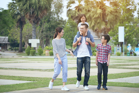 family running through garden at park, Happy family in the park, Mother, father and smiling