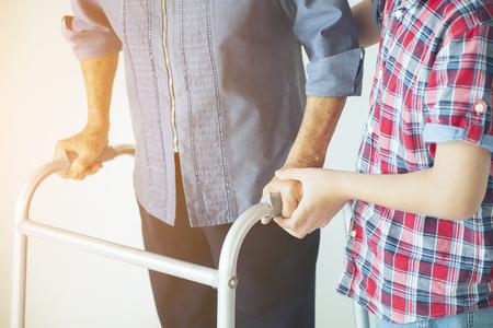 Babcia Starsza kobieta i wnuk z chodzikiem podczas rehabilitacji