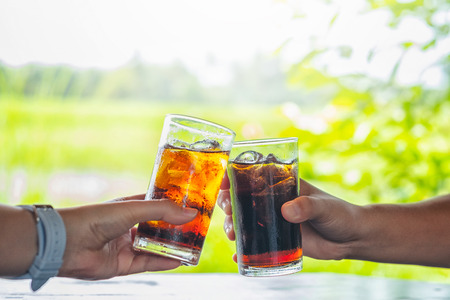 Men and Woman hand giving glass of cola.Glass of cola ,Soft drinks with ice, sweetheart or buddy Stock Photo