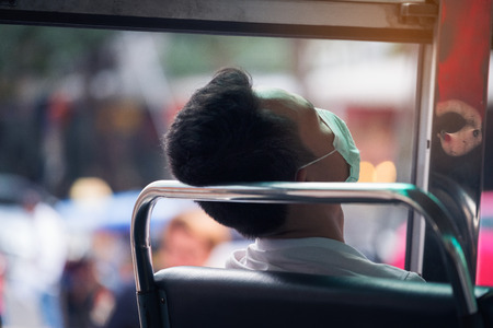 Man sleeping after be tried from hard work in public omnibus of bangkok in Bangkok, Thailand Stockfoto