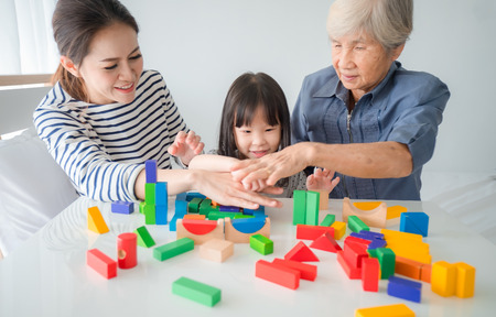 Multi-generation Female members of a family play wooden cubes colour (Geometric ladder) together with their grandmother, family time Stok Fotoğraf
