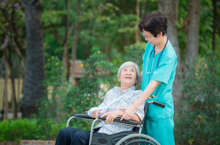Smiling caregiver Senior nurse take care a Senior patient on wheelchair for relaxing and looking around park Banco de Imagens