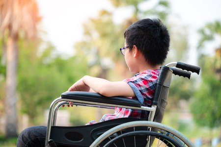 Alone young disabled man on wheelchair in the park, Patient is relaxing in garden decorations of the hospital feeling of missing someone, lonely 스톡 콘텐츠 - 124942895