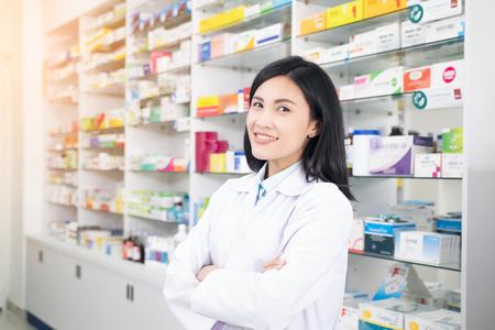 Farmacéutico sonriente hermosa de la mujer joven que hace su trabajo en farmacia.