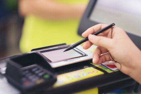 Close-up of consumer's women hand signing on a touch screen of credit card sale transaction receipt machine at supper market Banque d'images - 132142756