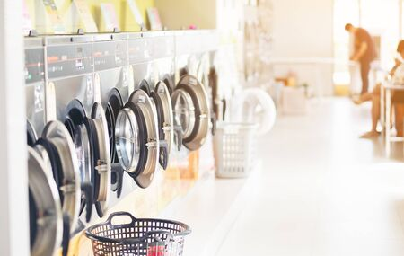 Row of industrial laundry machines , with laundry in a basket , Thailand Reklamní fotografie