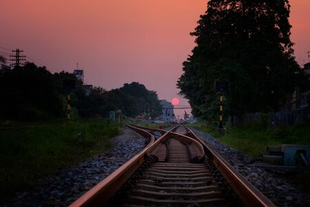 Railroad against beautiful sky at sunset. Industrial landscape with railway station, colorful gold sky, trees and grass, yellow sunlight. Railway junction. Heavy industry. Thailand
