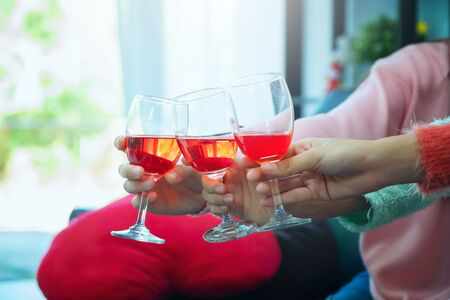 glasses of champagne close up, celebration, eating and holidays concept - hands clinking wine glasses, Focus on hands toasting red wine glass