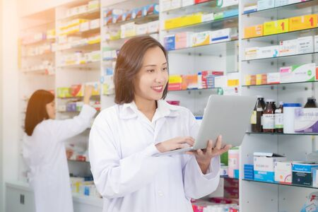 Asian pharmacist female using laptop computer and checklist inventory or reading information medication in pharmacy or drugstore. medicine, pharmaceutics, health care and people concept Foto de archivo - 132041007