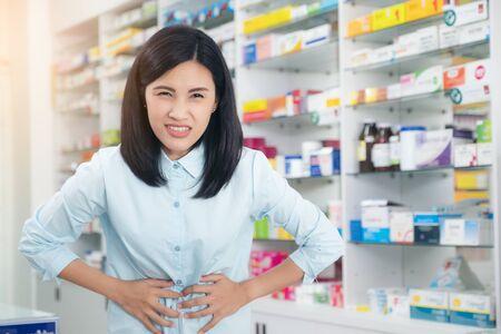 Patientin mit Magenschmerzen Hintergrundapotheke. Gesundheitswesen und medizinisches Konzept.