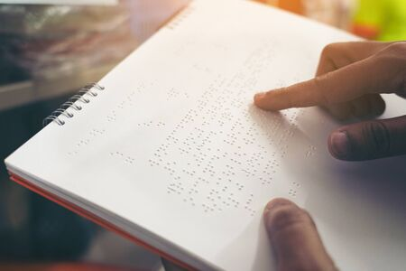 Close-up of fingers reading braille, Hand of a blind person reading some braille text of a braille book. Stock fotó