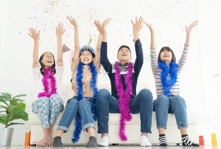 Group of children play with air balloons, confetti in light room on party, happy childhood concept