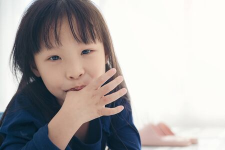 Asian kid cute girll sucking the finger her thumb