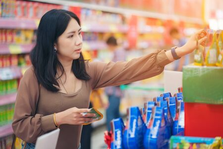 woman making shopping decision for sweet in supermarket, stands in store