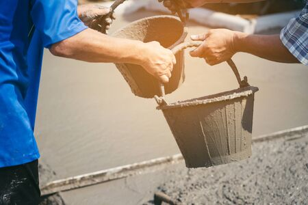 Construction workers helped cement bucket loaders to be introduced into a points set. Zdjęcie Seryjne