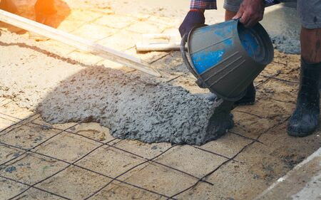 Close up of construction worker's gloved hands using trowel to scrape excess mix level with wood forms freshly poured concrete pad