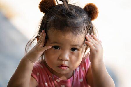 Closeup portrait of a cute little thai girl thinking, Close up portrait of a cute little girl Stock Photo