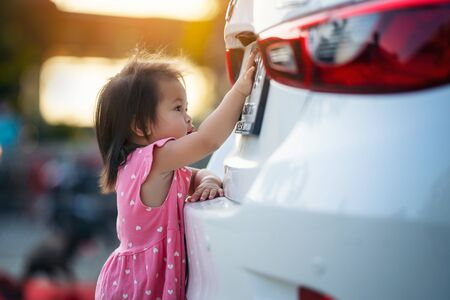 little girl looks license plate the car