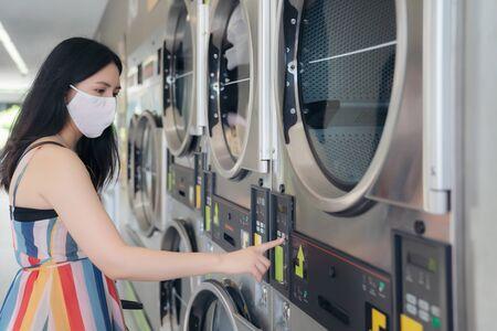 Beautiful woman with mask doing laundry at laundromat shop. Stock Photo