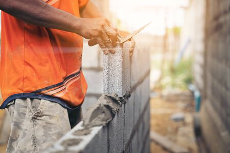 Worker building wall bricks with cement local Thailand Stock Photo