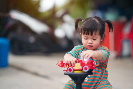 happy child girl with a car toy, cute kid playing outdoors. Stock Photo