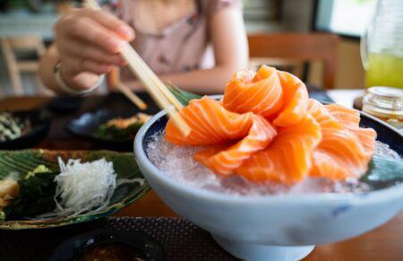 Salmon Sashimi on ice in the ceramic blow