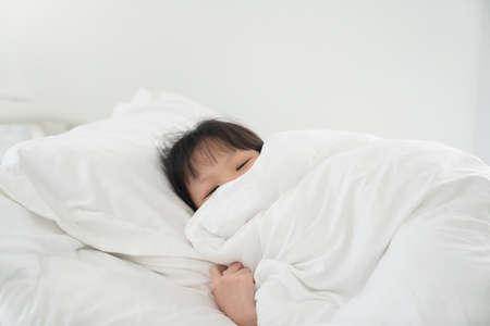 Cute asian girl lying under blanket on white bed Reklamní fotografie