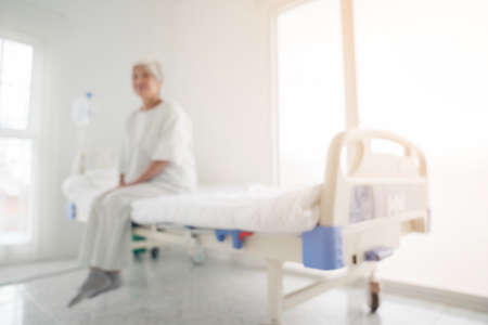Blurry background of senior woman sitting on bed in hospital ward