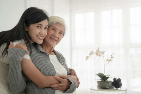 A nice girl and her grandmother enjoy sunny morning. Good time at home. Family playing in the living room Stock Photo