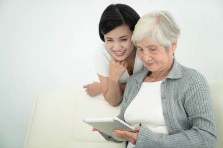 Ealry mother with daughter using digital tablet together at home. Smiling family looking at screen, shopping online
