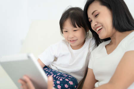 Young mother with children using digital tablet together at home. Smiling family looking at screen, shopping toys or watching cartoon online, Stock Photo