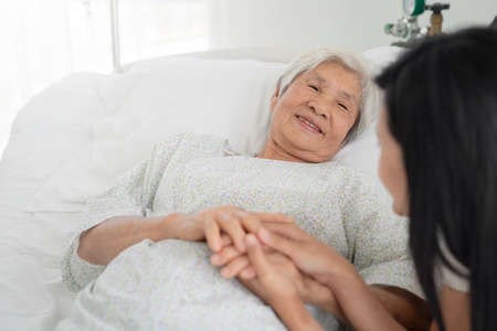 close up of patient grandfather and women holding hands in hospital bed