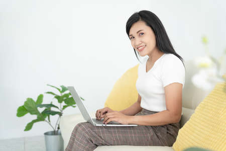Young lady with modern laptop sitting on sofa at home