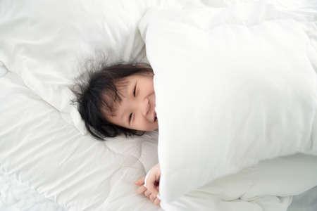 Cute asian girl lying under blanket on white bed