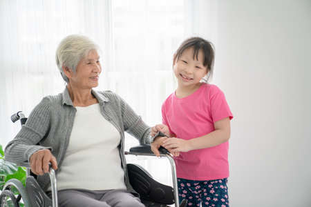 Elder patient woman on wheelchair waiting doctor with grandchild in hospital