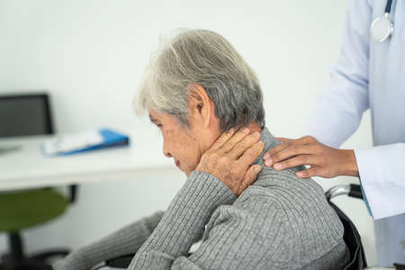 senior woman with neck pain in the medical office, Sick senior woman with back neck and shoulders pain on the joint and muscle. Stock Photo