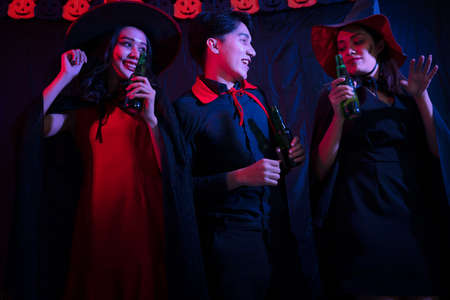 Young Thai People in Costumes Celebrating Halloween. Group of Young Happy Friends Wearing Halloween Costumes having Fun at Party in Nightclub by doing Scary faces.