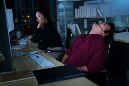 Thai asian call center business people get headache and migraine from working late night shift for helping assistance customer in workplace at night time 免版税图像