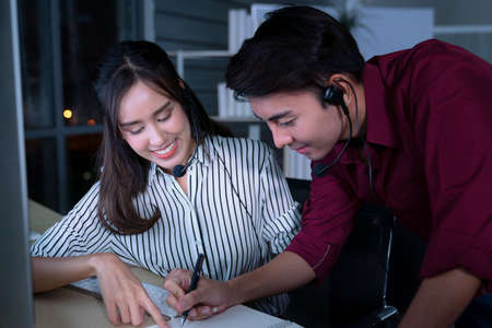 Young Thai Asian customer services care operators working night shift in call center for helping assistance client in workplace at night time