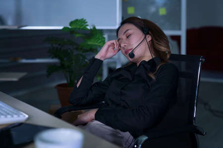 Thai asian women call center business people get headache and migraine from working late night shift for helping assistance customer in workplace at night time